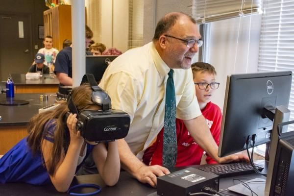 Michael Gallis, an associate professor of physics at Penn State Schuylkill, assists elementary and middle school students as they explore virtual reality at Kid's College, a five-day summer technology camp. Gallis has been continuing his work with VR for a new virtual reality-based course that will be taught this fall.